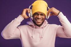 Afrikaanse mens in hoodie met hoofdtelefoons, gelukkige uitdrukking Muziek, mensen stock foto