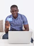 Afrikaanse mens met creditcard en laptop Stock Foto's