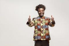 Afrikaanse mens in traditionele kleren toothy glimlach, die duimen tonen stock foto