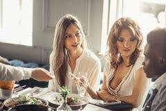 Afrikaanse mensen met mooie Kaukasische meisjes die lunch samen in koffie hebben Stock Foto