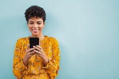 Afrikaanse modieuze vrouw die smartphone met behulp van stock afbeelding