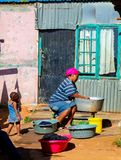 Afrikaanse moeder en kindwaskleren in Soweto-Ne Met een laag inkomen stock afbeelding