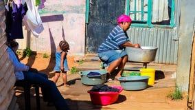 Afrikaanse moeder en kindwaskleren in Soweto-Ne Met een laag inkomen stock fotografie