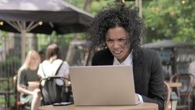 Afrikaanse Onderneemster in Schok door Resultaten op Laptop in Openluchtkoffie stock video