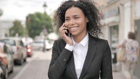 Afrikaanse Onderneemster Talking op Telefoon die zich openlucht op Voetpad bevinden stock footage