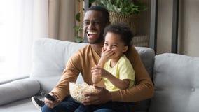 Afrikaanse vaderholding op overlapping weinig zoonsfamilie het letten op film royalty-vrije stock afbeelding