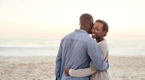 Afrikaanse vrouw die haar vriend op een strand omhelzen bij zonsondergang stock fotografie