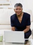 Afrikaanse vrouw die laptop op bank thuis met behulp van Royalty-vrije Stock Foto