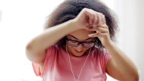 Afrikaanse vrouw die met oortelefoons aan muziek luisteren stock footage
