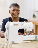 Afrikaanse vrouw die naaimachine met behulp van Royalty-vrije Stock Foto's