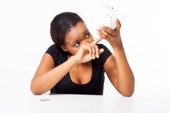 Afrikaanse vrouw die piggybank kijken stock afbeeldingen