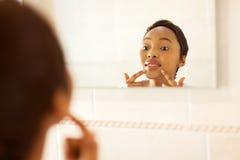 Afrikaanse vrouw die pukkel controleren Stock Foto