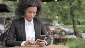 Afrikaanse Vrouw die Smartphone gebruiken die in Openluchtkoffie zitten stock video