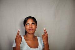 Afrikaanse vrouw die terwijl het kruising van haar vingers bidden Royalty-vrije Stock Afbeeldingen