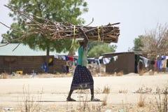 Afrikaanse vrouw die zware lading dragen Royalty-vrije Stock Afbeelding