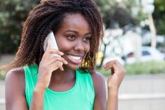 Afrikaanse vrouw in een groen overhemd openlucht bij telefoon Stock Afbeeldingen