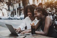 Afrikaanse vrouw en Japanse man die netbook in straatbar gebruiken royalty-vrije stock foto's