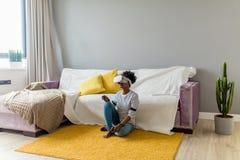 Afrikaanse vrouw het letten op video die VR-glazen met afstandsbediening thuis gebruiken stock fotografie