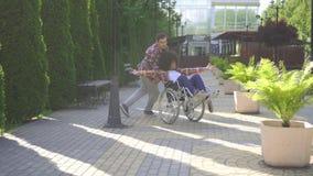 Afrikaanse vrouw met de gehandicapten van een afrokapsel in een rolstoel in het park voor een gang met een vriend die pret hebben stock video