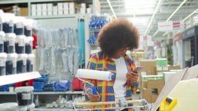 Afrikaanse vrouw met een afrokapsel met de telefoon in hand in de winkel in de afdeling allen voor reparatie stock footage