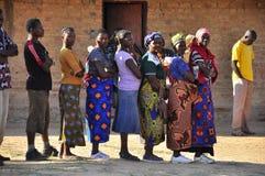 Afrikaanse vrouwen die aan stem bij opiniepeilingspost een rij vormen stock foto's