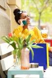 Afrikaanse vrouwenzitting op bank en het spreken op mobiele telefoon Royalty-vrije Stock Afbeeldingen
