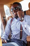 Afrikaanse zakenman in de auto die op smartphone spreken stock afbeeldingen