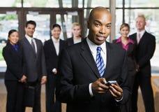 Afrikaanse zakenman die celtelefoon met behulp van stock foto
