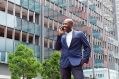 Afrikaanse zakenman die op mobiele telefoon in de stadsstraat spreken Stock Afbeeldingen