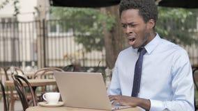 Afrikaanse Zakenman in Schok door Resultaten op Laptop in Openluchtkoffie stock videobeelden