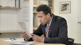Afrikaanse Zakenman in Schok terwijl het Gebruiken van Tablet stock footage