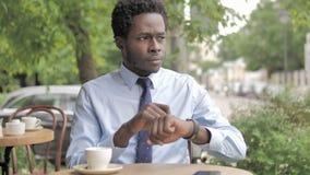 Afrikaanse Zakenman Using Smartwatch, die in Openluchtkoffie zitten stock footage