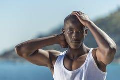 Afrikaanse zwarte mens die wit vest en blauwe korte jeans dragen Royalty-vrije Stock Foto's