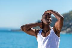 Afrikaanse zwarte mens die wit vest en blauwe korte jeans dragen Stock Afbeeldingen
