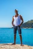 Afrikaanse zwarte mens die wit vest en blauwe korte jeans dragen Royalty-vrije Stock Afbeelding