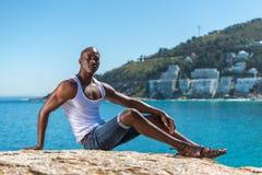 Afrikaanse zwarte mens die wit vest en blauwe korte jeans dragen Stock Fotografie