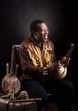 Afrikaanse zwarte mens met etnisch muzikaal instrument stock foto's
