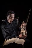 Afrikaanse zwarte mens met etnisch muzikaal instrument stock foto