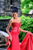 Afrikan-Afrikan-amerikanen flickan i en röd klänning med dreadlocks på hennes huvud och skor i hennes hand står i parkera Arkivfoton