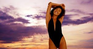 Afrikanerin in der Badebekleidung, die unter buntem Himmel steht Lizenzfreie Stockfotografie