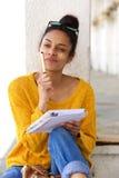 Afrikanerin, die außerhalb des Denkens und des Schreibens in Buch sitzt lizenzfreie stockbilder