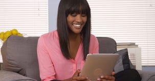 Afrikanerin, die Auflage auf Couch verwendet Lizenzfreie Stockfotos
