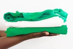 Afrikanerin, die einen Stapel Kleidung in zwei Händen hält lizenzfreie stockfotos