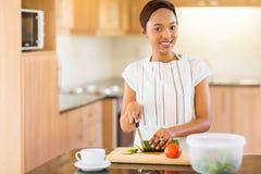 Afrikanerin, die Gemüse hackt Stockbilder