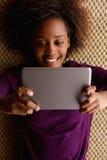 Afrikanerin, die sich mit digitaler Tablette hinlegt Lizenzfreie Stockfotos