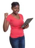 Afrikanerin im roten Hemdeinkaufen am Internet Stockfotos