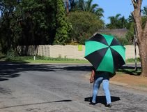 Afrikanerin mit buntem Regenschirm stockbild