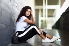 Afrikanerin mit der schwarzen gelockten Frisur, die auf st?dtischem Boden sitzt lizenzfreie stockbilder