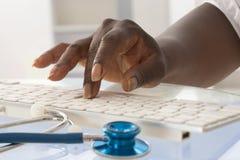 Afrikanische Ärztinhand, die auf Tastatur schreibt Lizenzfreie Stockfotos