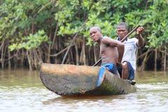 Afrikanische Fischer, die in den Mangroven rudern Lizenzfreie Stockbilder
